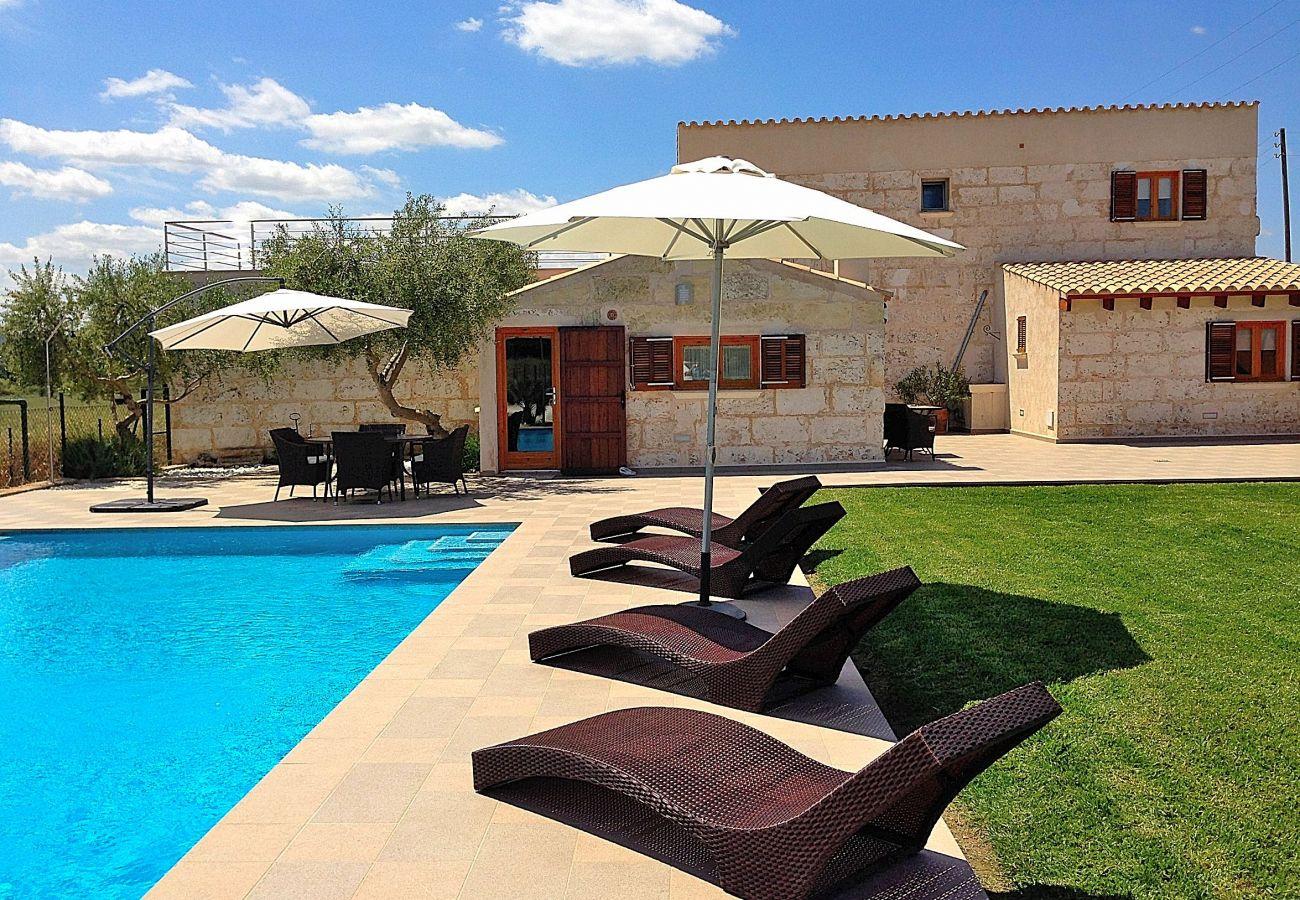 Foto de casa con piscina y hamacas en el césped