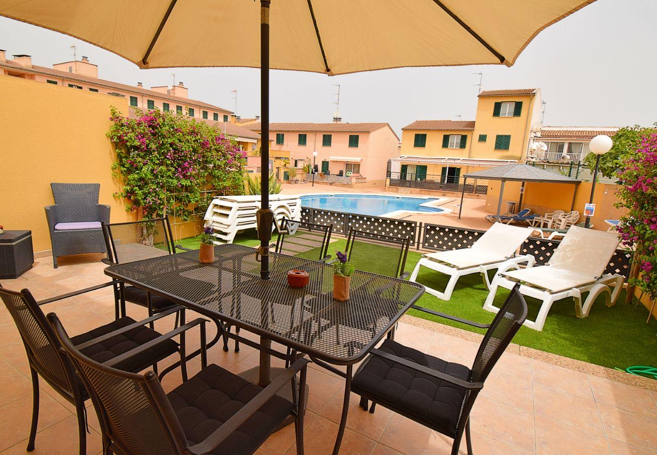 terraza con jardín al lado de la piscina
