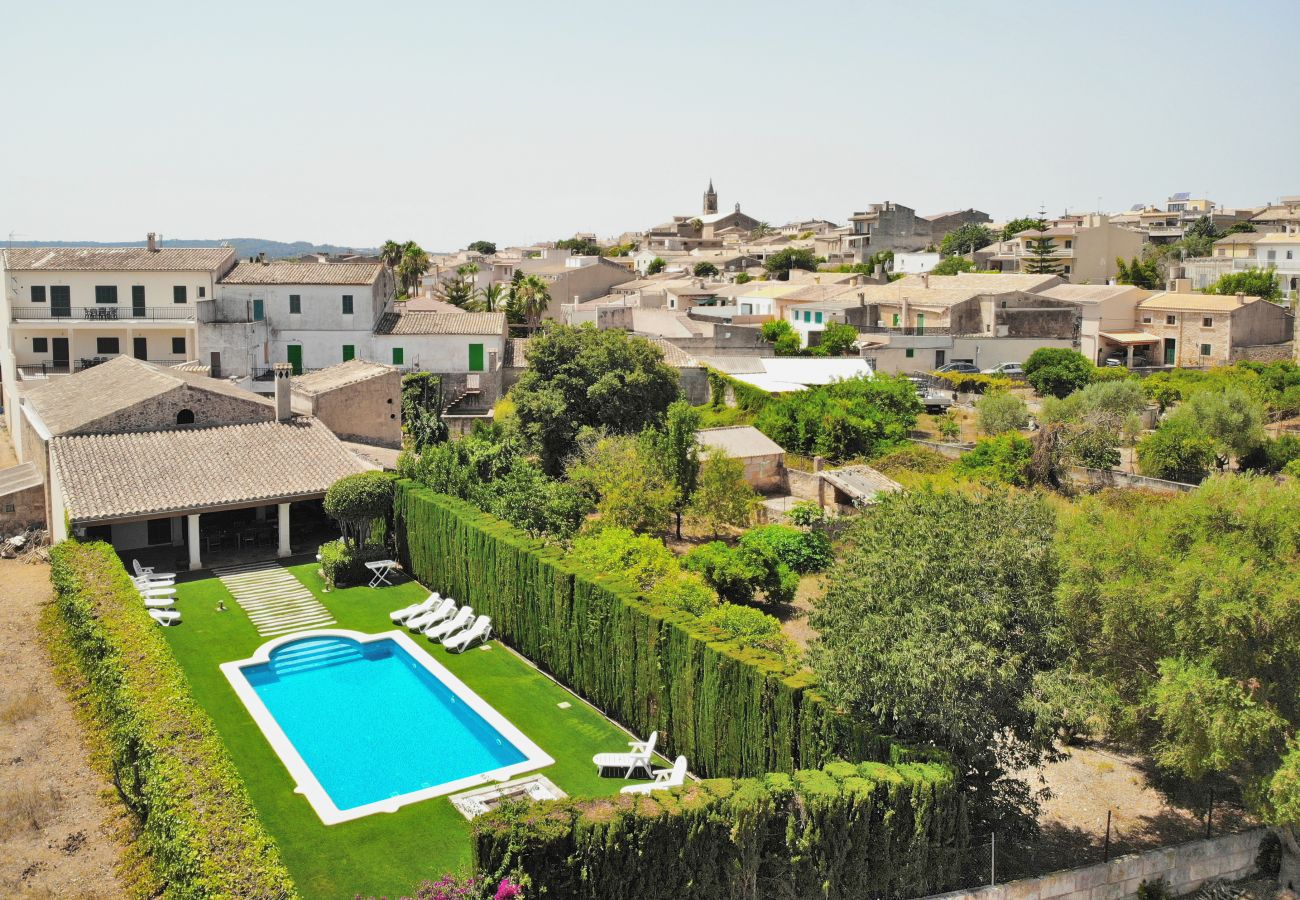 Blick auf das Schwimmbad der Villa Tofollubi mit dem Dorf Llubi.