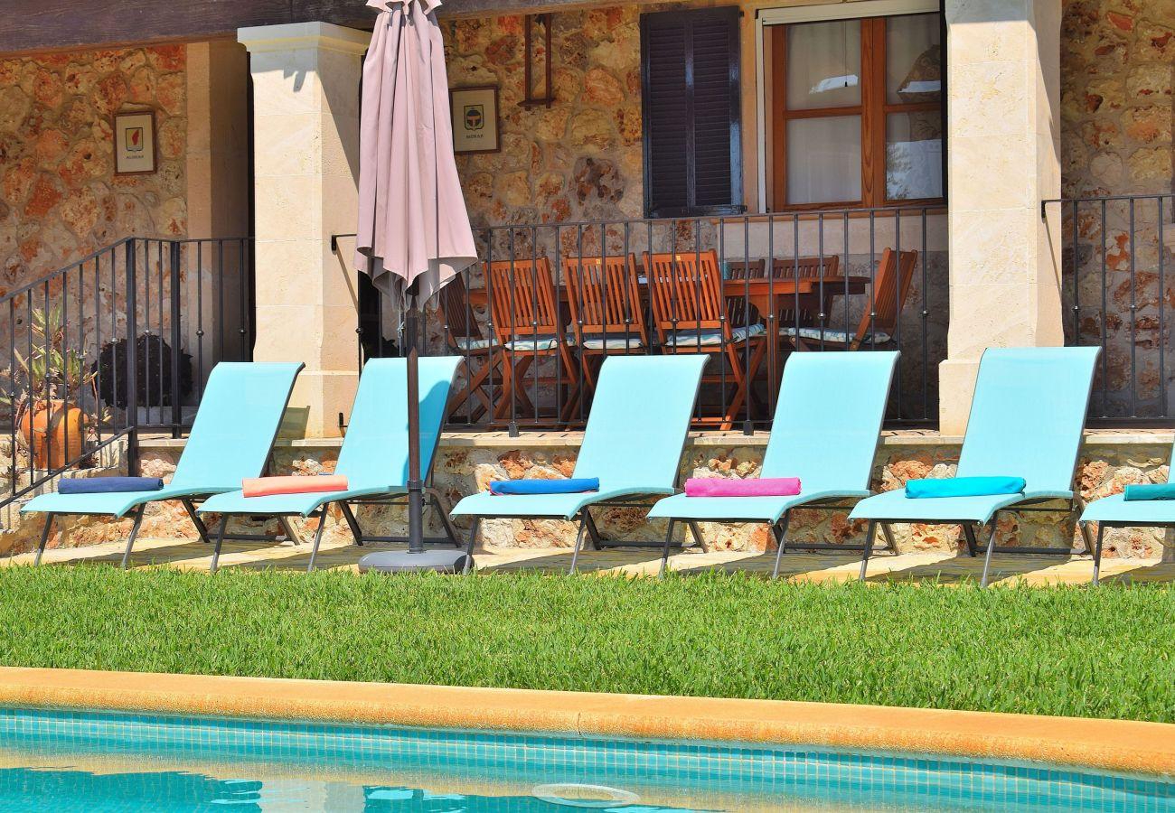 Ferienhaus mit Liegestühlen am Schwimmbad